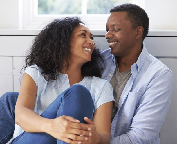 African American couple smiling and staring at eachother.